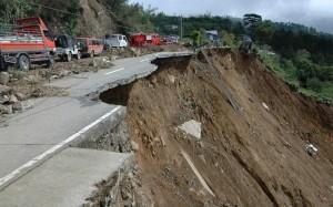 Vehicles travel along the damaged Halsema Highway after landslides triggered by typhoon Parma in Benguet province